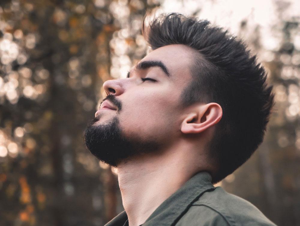 мужчина правильно дышит в лесу